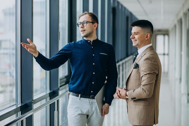 Dwaj koledzy w biurze, stojąc z laptopem