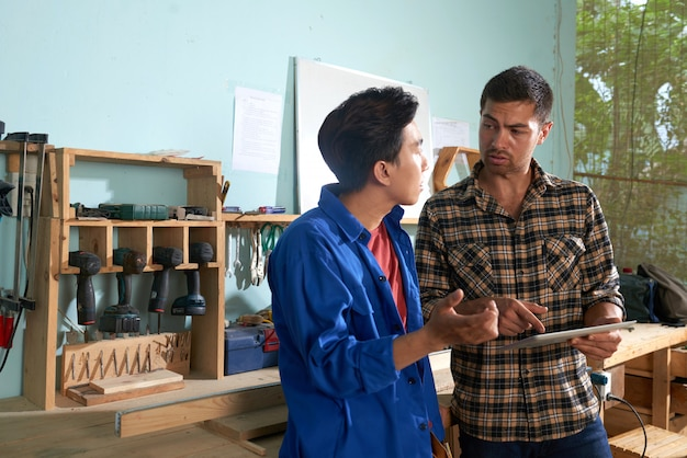 Dwaj koledzy współpracują w warsztacie stolarskim przy użyciu komputera typu tablet