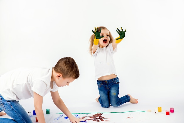 Dwaj ładni przyjaciele, chłopiec i dziewczynka, rysują farbami