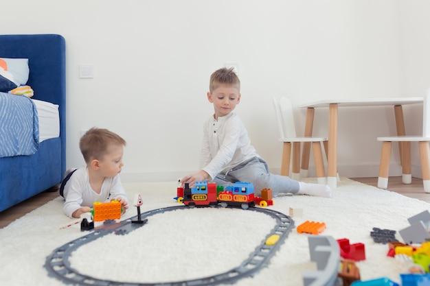 Dwaj mali bracia bawią się w swoim żłobku, bawią się konstruktorem i trenują