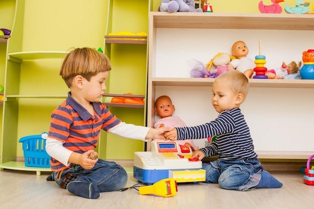 Dwaj mali chłopcy grają w przedszkolu rolę kasjera i kupca
