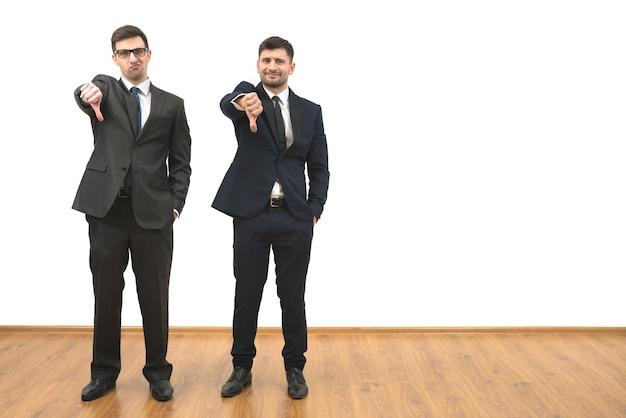 Dwaj mężczyźni kciukiem w dół na tle białej ściany