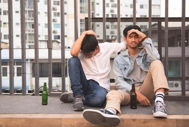 Dwaj mężczyźni pijani i siedzą razem na ulicy