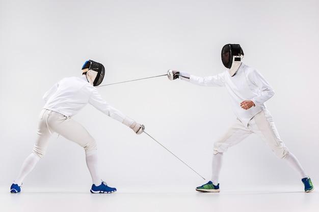 Dwaj mężczyźni ubrani w szermierkę ćwiczyli mieczem przeciwko szarości
