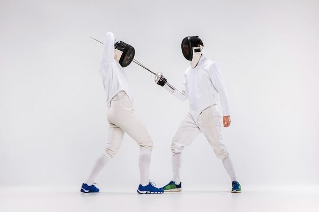 Dwaj mężczyźni w strojach szermierczych ćwiczący z mieczem na szaro