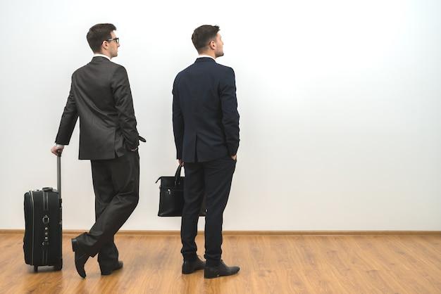 Dwaj mężczyźni z torbami stoją na białym tle ściany