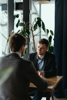 Dwaj młodzi biznesmeni dyskutuje coś