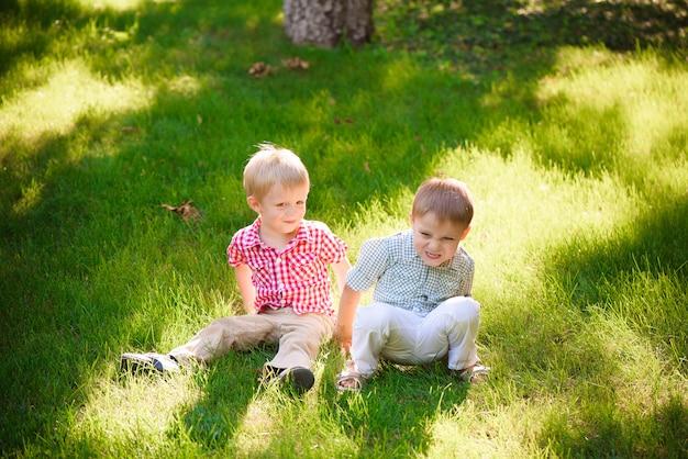 Dwaj młodzi chłopcy spacerują i relaksują się w parku.
