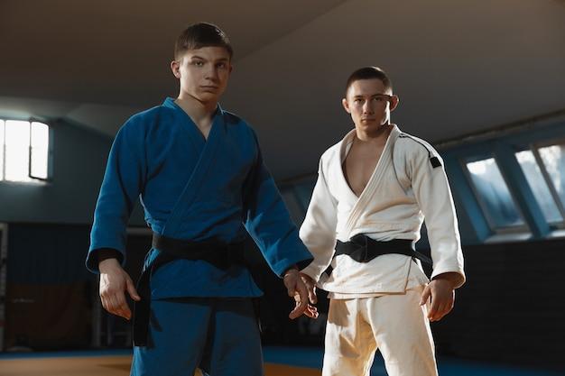 Dwaj młodzi kaukascy zawodnicy judo w biało-niebieskim kimonie z czarnymi pasami pozują pewnie na siłowni, silni i zdrowi. ćwiczenie umiejętności walki w sztukach walki. pokonywanie, osiąganie celu.