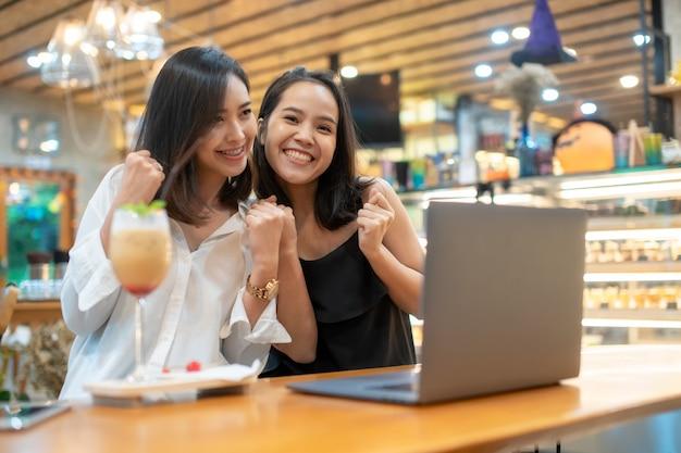 Dwaj podekscytowani przyjaciele kupują online za pomocą karty kredytowej i laptopa, mediów społecznościowych i koncepcji zakupów online.