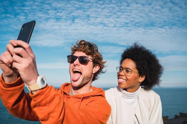 Dwaj przyjaciele biorący selfie z smartpone