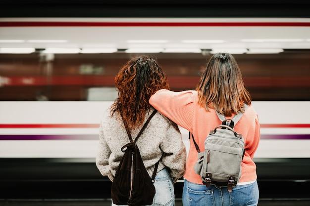 Dwaj przyjaciele czekają zrelaksowani i beztroscy na stacji przed złapaniem pociągu. fotografia podróżnicza