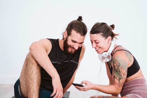 Dwaj przyjaciele na siłowni słuchają muzyki na telefonie komórkowym i zestawie słuchawkowym i dobrze się bawią