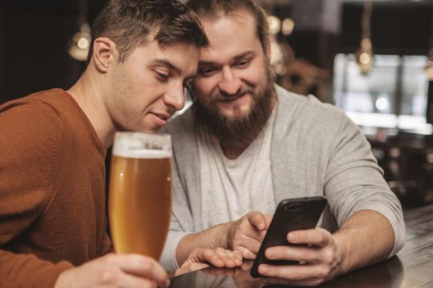 Dwaj przyjaciele rozmawiają przy piwie w pubie
