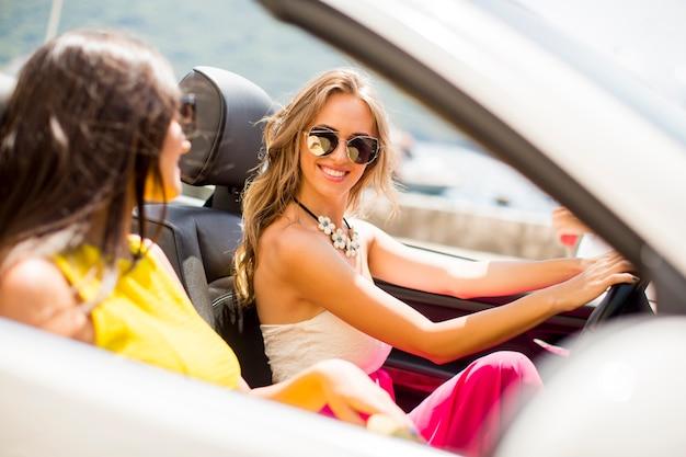 Dwaj przyjaciele szczęśliwy w biały samochód kabriolet jazdy i szuka wolności i zabawy
