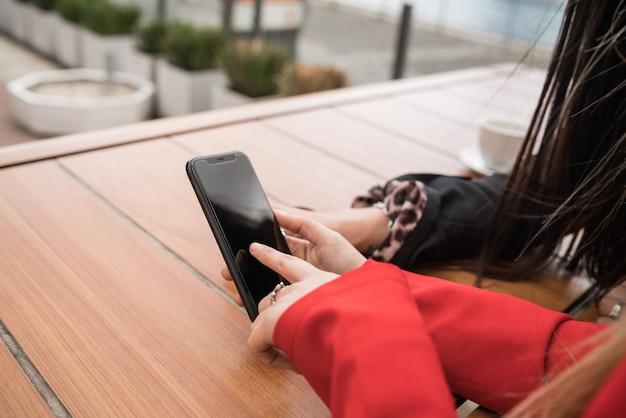 Dwaj przyjaciele używają telefonu komórkowego, siedząc w kawiarni.