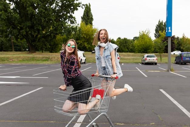 Dwaj przyjaciele zabawy na parkingu w supermarkecie
