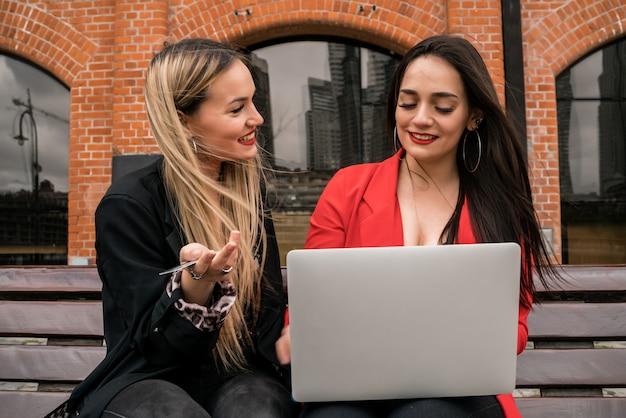 Dwaj przyjaciele zakupy online za pomocą karty kredytowej i laptopa.