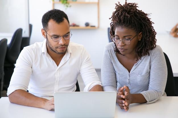 Dwaj różnorodni biznesowi koledzy dyskutuje projekt