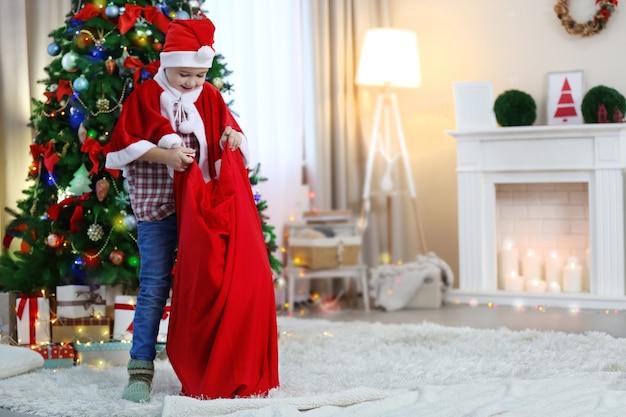 Dwaj śliczni mali bracia bawiący się torbą świętego mikołaja na tle dekoracji świątecznych