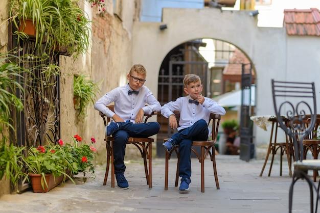 Dwaj słodcy chłopcy rozmawiają, siedząc na drewnianych krzesłach. chłopcy naśladują rodziców biznesmenów. chłopcy siedzą na krzesłach ze skrzyżowanymi nogami i zamyślonymi twarzami.
