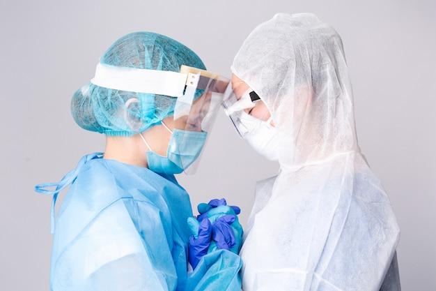 Dwaj smutni lekarze pocieszają się nawzajem poza koncepcją pandemii i opieki zdrowotnej na oddziale intensywnej terapii