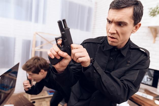 Dwaj strażnicy trzymają broń i walkie-talkie.