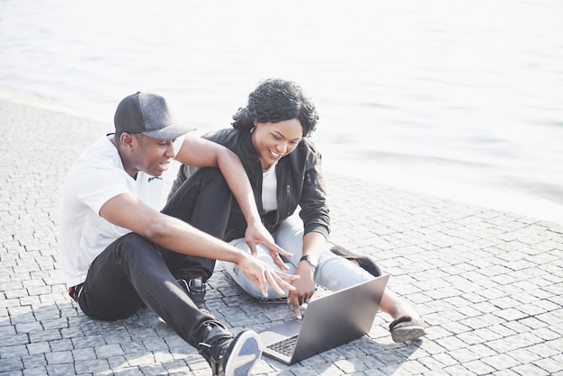 Dwaj szczęśliwi przyjaciele studentów lub partnerów biznesowych siedzą na zewnątrz i cieszą się laptopem