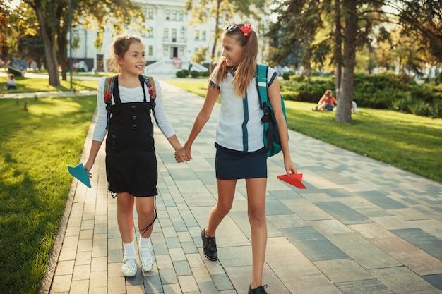 Dwaj szkolni przyjaciele chodzą po lekcjach w parku w pobliżu szkoły