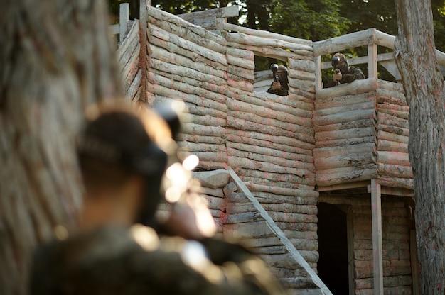 Dwaj wojownicy paintballa strzelają z broni palnej ze schroniska na placu zabaw