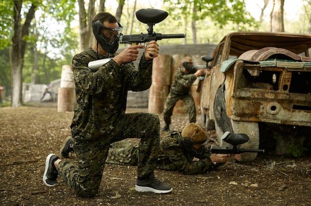 Dwaj wojownicy płci męskiej celują z pistoletami do paintballa