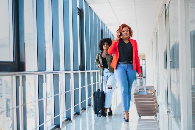 Dwie afrykańskie dziewczyny z walizkami na lotnisku pojęcie podróży i wakacji