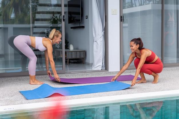 Dwie aktywne kobiety azjatki i kaukaski wychodzą poza praktykę jogi w luksusowej willi przy basenie