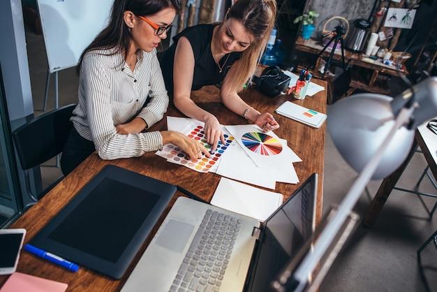 Dwie architektki pracujące razem przy użyciu próbek kolorów, siedząc przy biurku z laptopem.