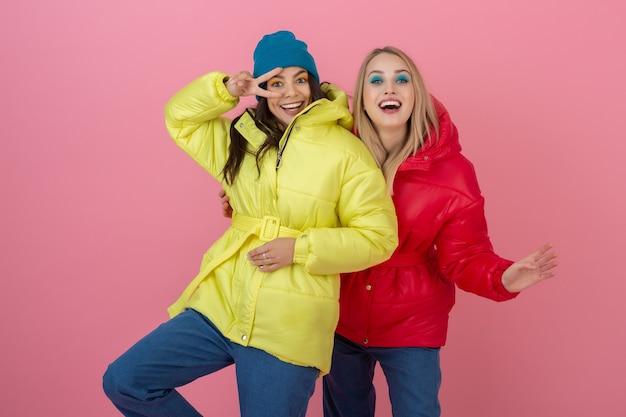 Dwie atrakcyjne aktywne kobiety pozujące na różowej ścianie w kolorowej zimowej kurtce puchowej w jasnoczerwonym i żółtym kolorze, przyjaciele dobrze się bawią, trend w modzie na ciepły płaszcz, szalone śmieszne twarze