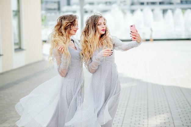 Dwie atrakcyjne bliźniaczki w identycznych lekkich sukienkach na tle miasta