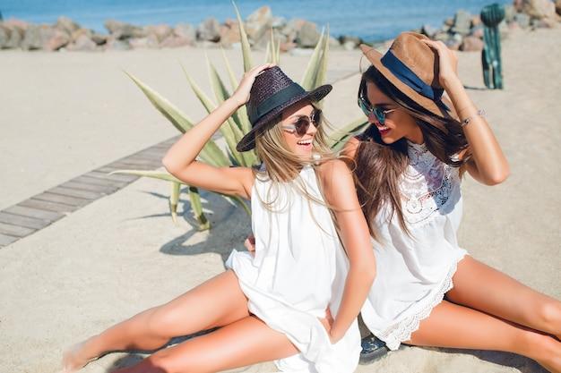Dwie atrakcyjne brunetki i blondynki z długimi włosami siedzą na plaży w pobliżu morza. trzymają kapelusze i uśmiechają się do siebie.