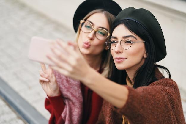 Dwie atrakcyjne dziewczyny co selfie siedząc razem