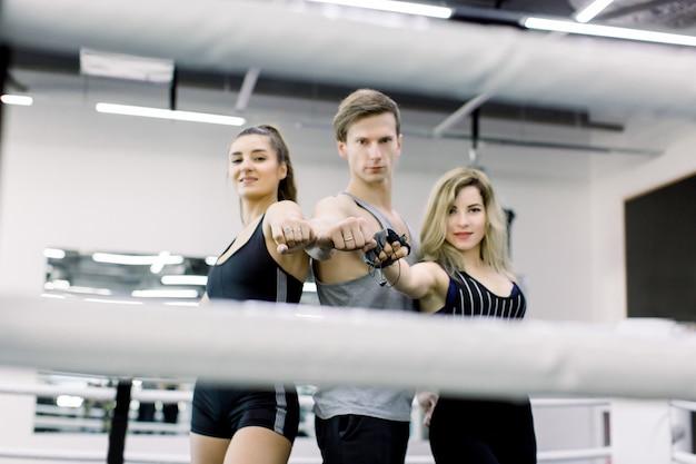 Dwie atrakcyjne dziewczyny i przystojny młody chłopak pozują na ringu bokserskim w pomieszczeniu, wyciągając ręce do przodu. fitness, koncepcja boksu