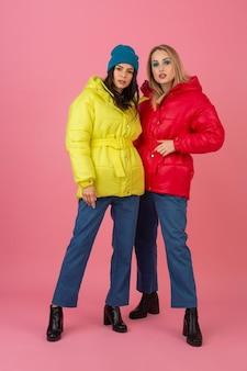 Dwie atrakcyjne dziewczyny pozują na różowym tle w kolorowej zimowej kurtce puchowej w jasnoczerwonym i żółtym kolorze