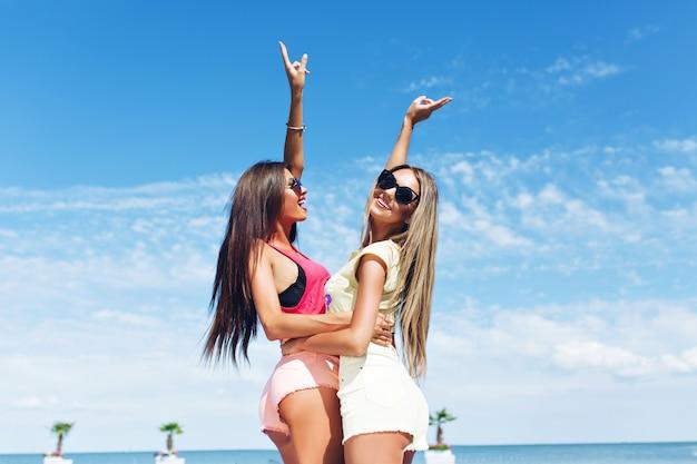 Dwie atrakcyjne dziewczyny z długimi włosami przytulają się i uśmiechają na zewnątrz w pobliżu morza. zobacz na tle nieba.
