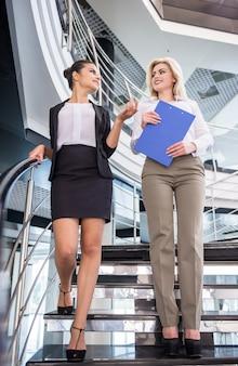 Dwie atrakcyjne kobiety biznesu schodzą po schodach.