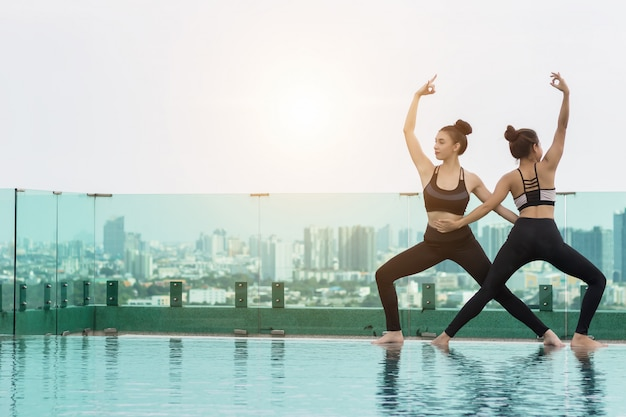 Dwie atrakcyjne kobiety grają jogę. przy basenie dla jej dobrego zdrowia