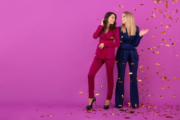 Dwie atrakcyjne kobiety świętują nowy rok na fioletowej ścianie w stylowych kolorowych wieczorowych garniturach w kolorze fioletowym i niebieskim, przyjaciele dobrze się bawią, trend w modzie, nastrój imprezowy ze złotym konfetti