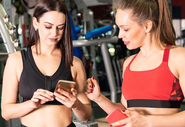Dwie atrakcyjne kobiety w siłowni z inteligentnego telefonu