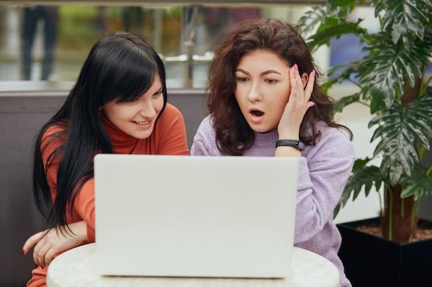 Dwie atrakcyjne kobiety z białym laptopem siedzą przy kawie, patrząc na ekran notebooka ze zdumioną mimiką twarzy, podczas odpoczynku w kawiarni widzą coś ciekawego.