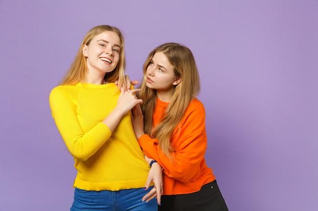 Dwie atrakcyjne młode blond siostry bliźniaczki dziewczyny w żywych kolorowych ubraniach stojących, odizolowane na pastelowej fioletowej niebieskiej ścianie. koncepcja życia rodzinnego osób.