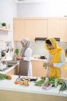 Dwie atrakcyjne młode kobiety muzułmańskie przygotowujące razem kolację iftar
