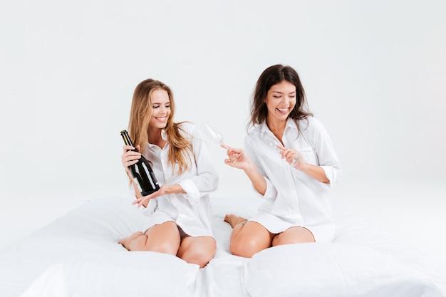 Dwie atrakcyjne młode kobiety na przyjęciu z butelką szampana w łóżku