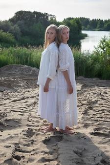 Dwie atrakcyjne młode siostry bliźniaczki pozowanie na piaszczystej plaży w eleganckie białe ubrania